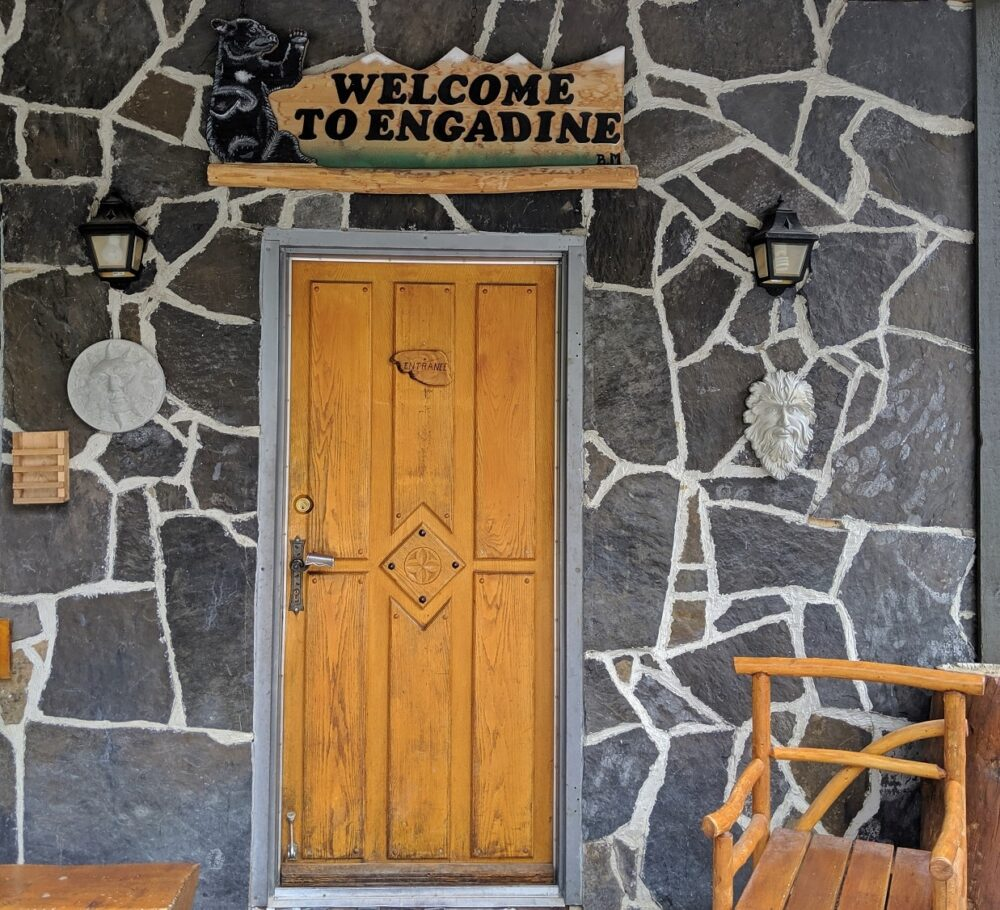 Welcome to Engadine sign above wooden door, stone building