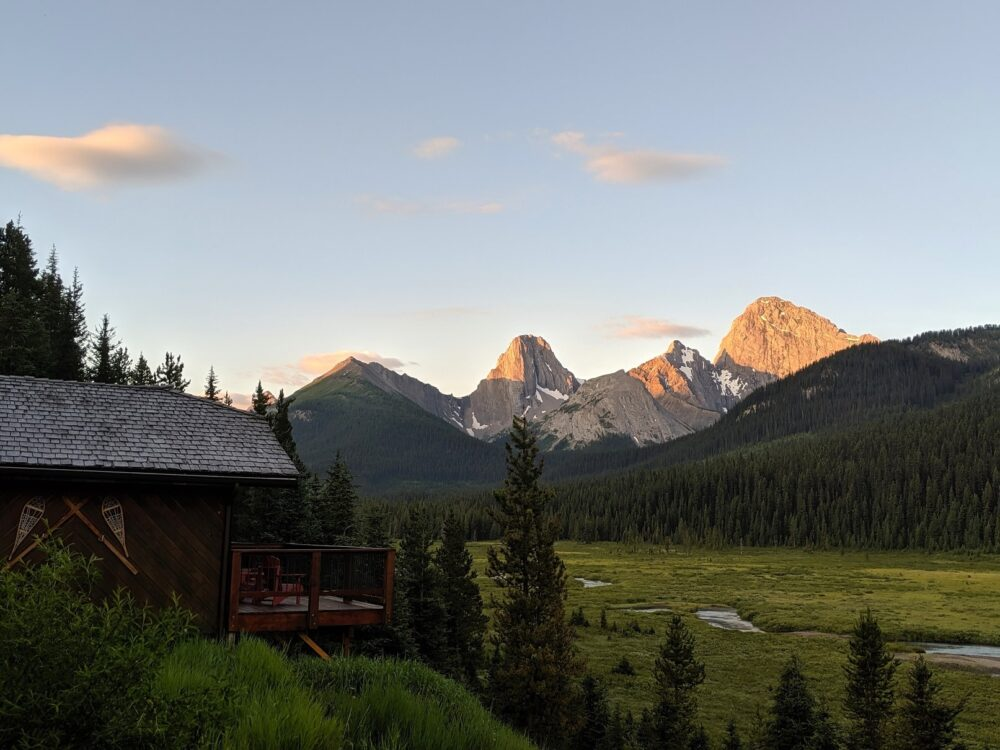 Wooden cabin on left with sun topped mountains above a meadow at Mount Engadine Lodge