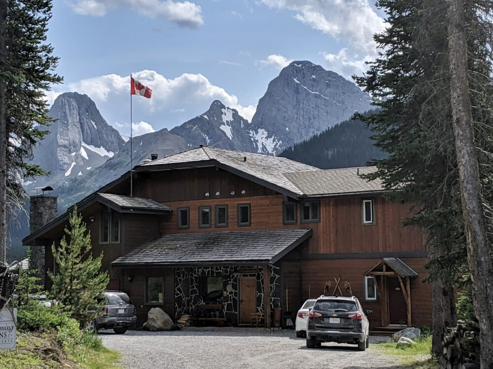 Main wooden building of Mount Engadine Lodge with mountain range behind and Canadian flag flying on roof