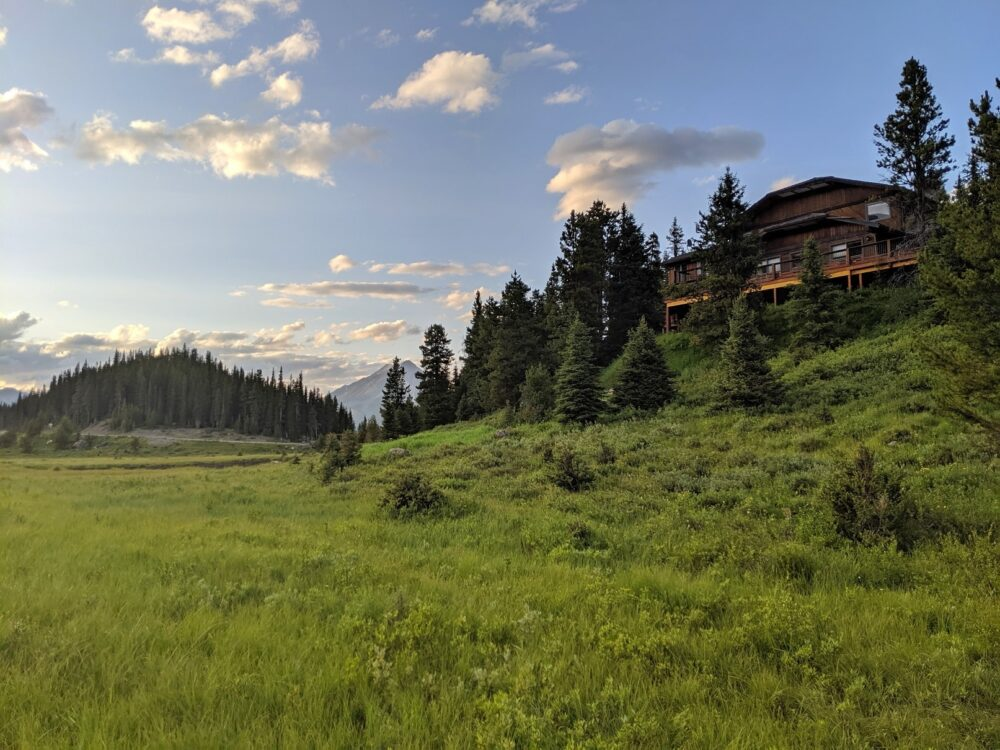Mount Engadine Lodge building above lush meadow in the Kananaskis Valley, Alberta