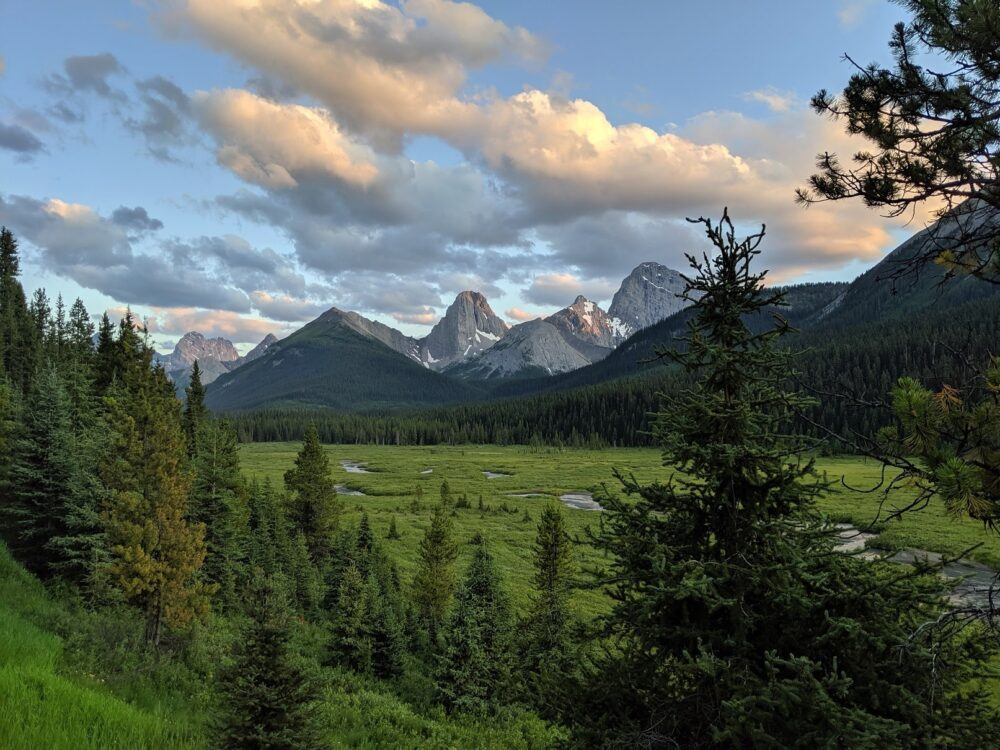Sunset above a mountain range backdropping a meadow, outside of Mount Engadine Lodge in the Kananaskis Valley, Alberta