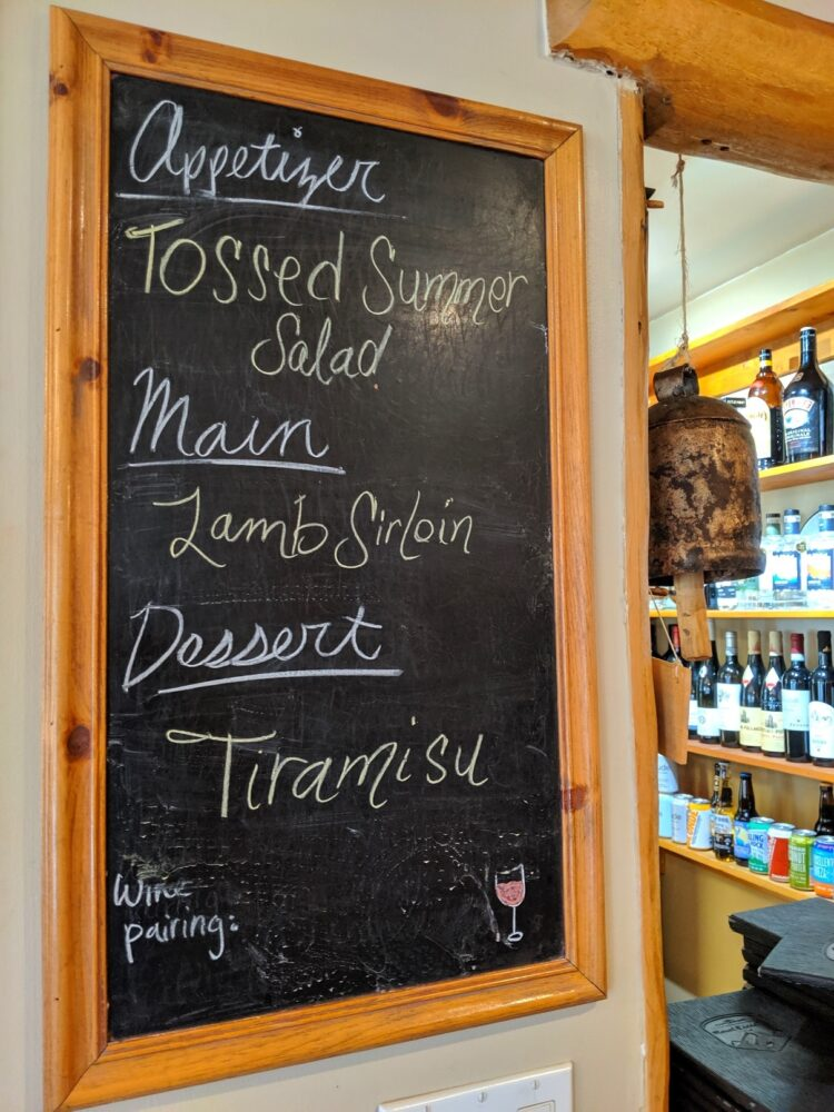 Blackboard with written menu (tossed summer salad, lamb sirloin and tiramisu) next to bar window, with bottles of wine lined up on shelves