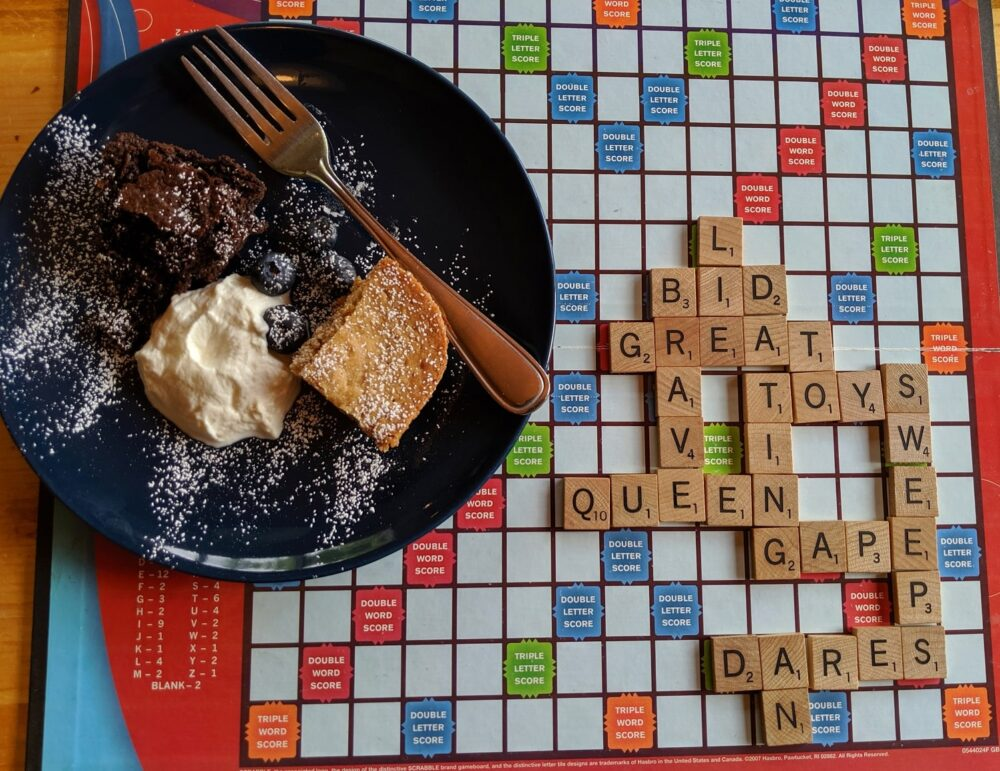 Scrabble board with plate of cake and cream on top, at Mount Engadine Lodge afternoon tea