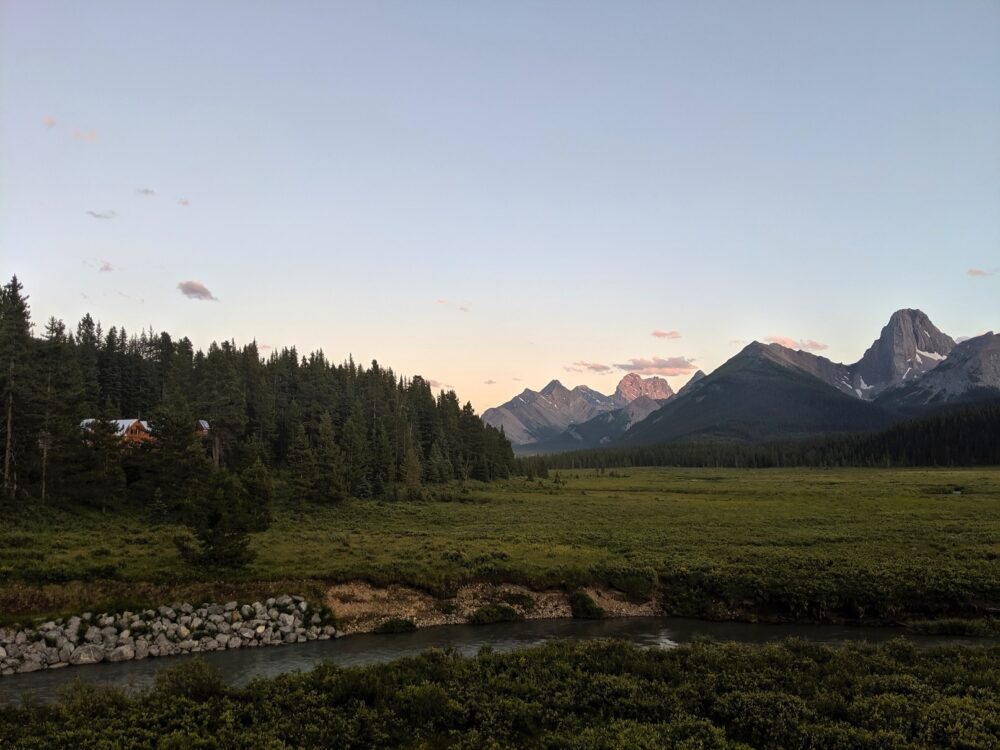Engadine Lodge sits on the left in front of a meadow and backdrop of mountain peaks, sunset