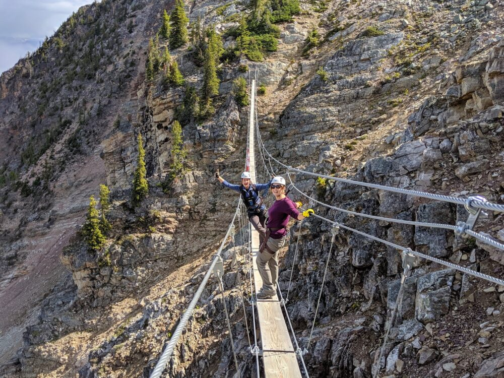 Gemma and guide Lenka crossing a suspension bridge on the Kicking Horse Via Ferrata