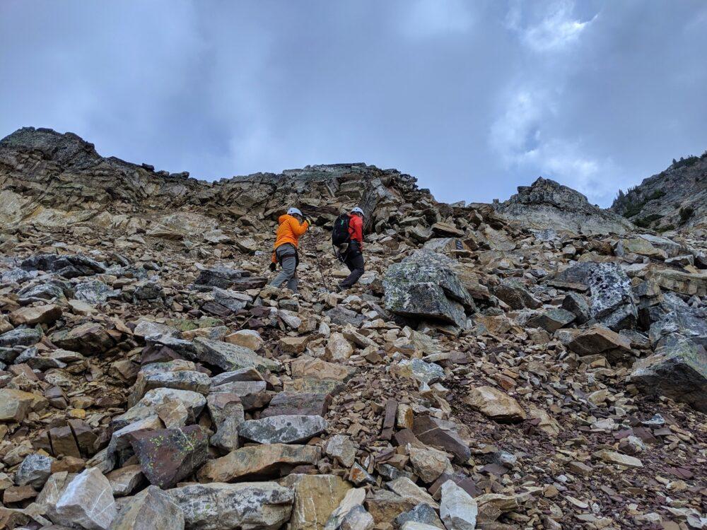 Gemma and Lenka walking along rocky path towards the Via Ferrata at Kicking Horse Mountain Resort