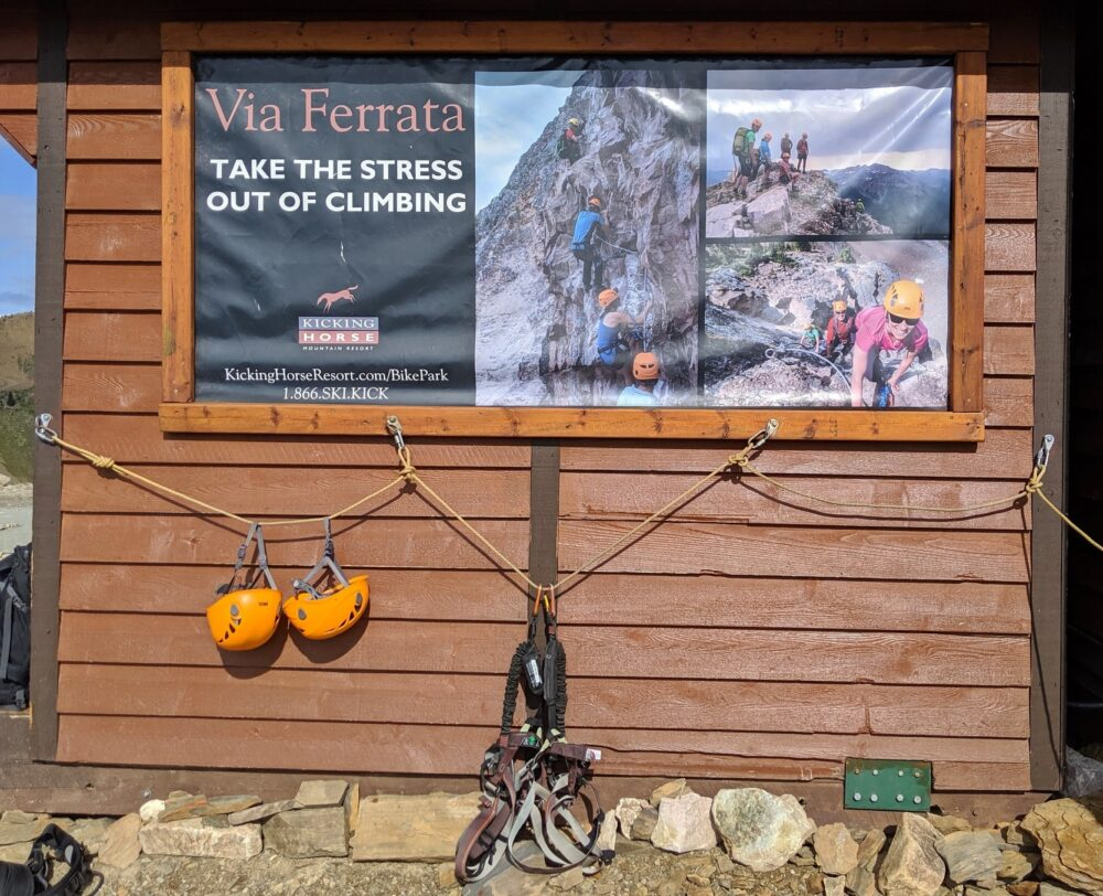 Climbing helmets hanging in front of Via Ferrata poster, on wooden hut
