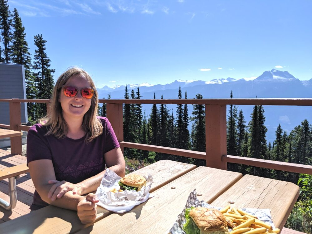 Gemma sat at patio table with views of mountains beyond, burgers and fries on table