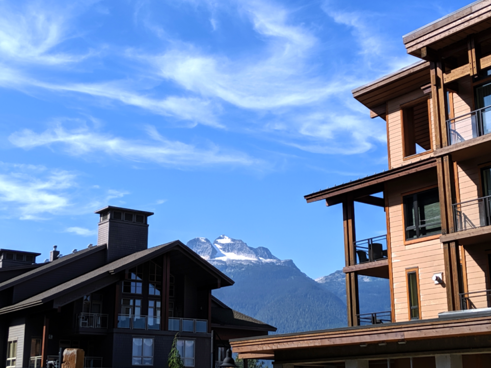 Wooden lodge buildings with Monashee mountains in background