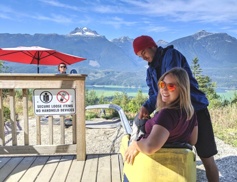 Gemma sat in yellow car at start of Revelstoke Mountain Coaster ride, with attendant buckling seatbeat