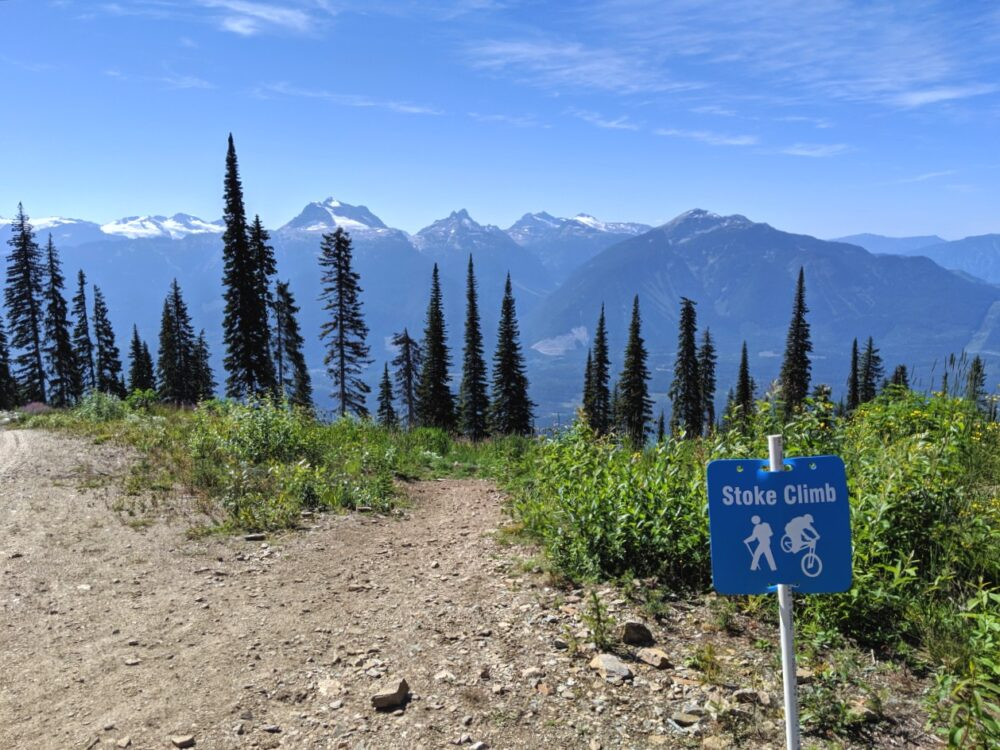 Hiking trail heading towards mountains with blue 'Stoke Climb' sign