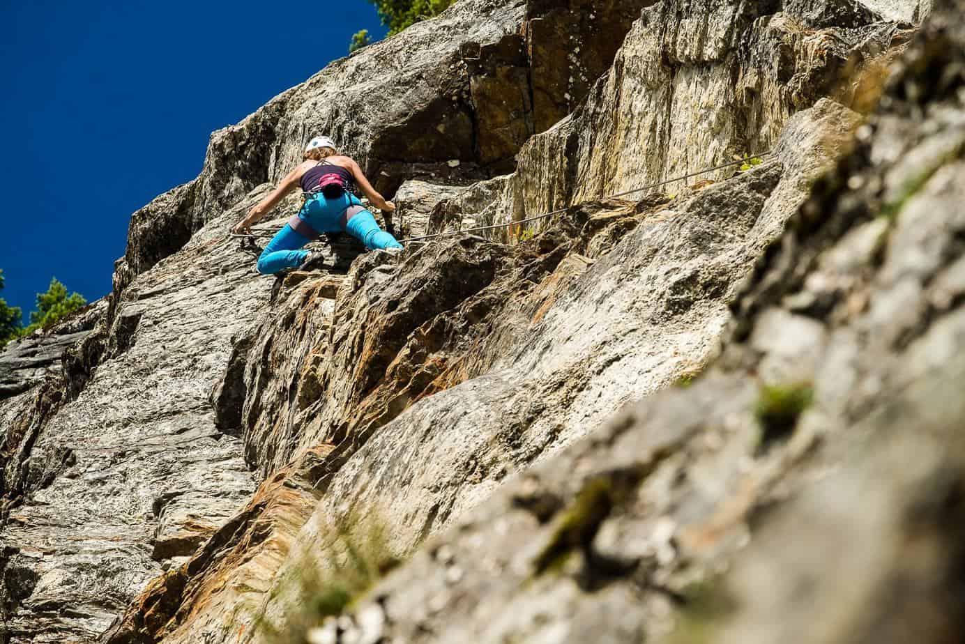 Female climber ascending rock near Revelstoke