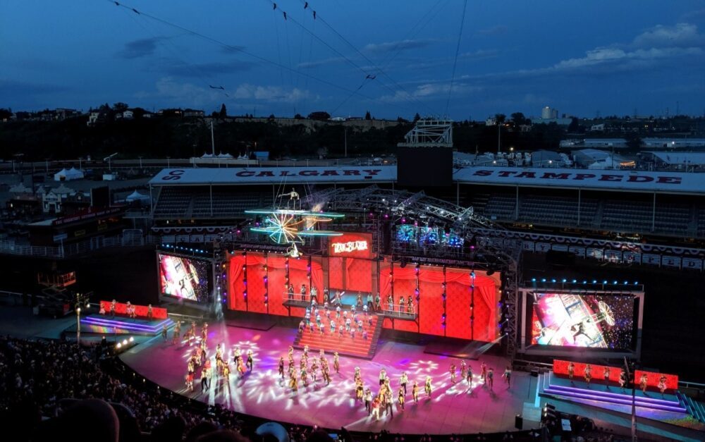 Lit up Calgary Stampede stage with dancers and big screens