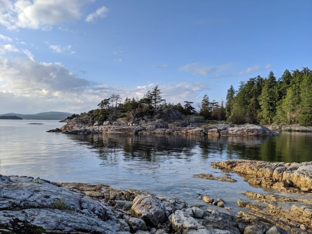 Calm coastal inlet with rocky shoreline on the Sunshine Coast, specifically Desolation Sound