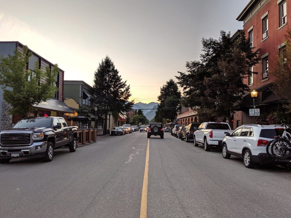 Middle of road view of downtown Revelstoke with mountains in background and older heritage buildings