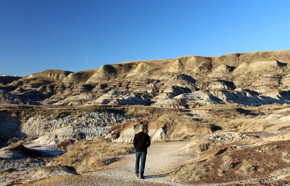JR on hiking path with rugged badlands landscape near Drumheller, Alberta