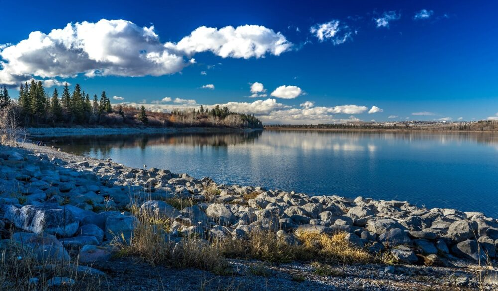 rocky shoreline next to reservoir in Calgary, blue skies