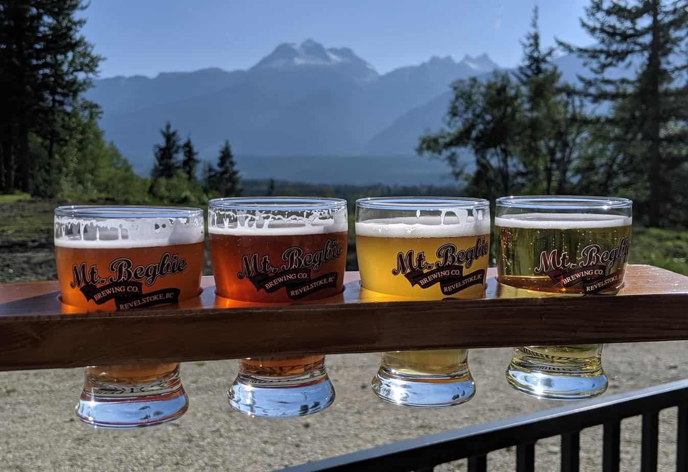 Four tasting glasses of beer in front of mountain view, Mt Begbie Brewing Company