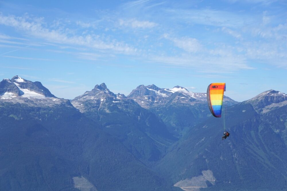 A colourful paraglider flies in front of a range of mountains
