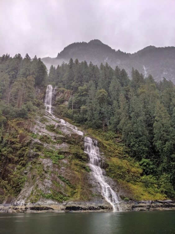 Rock and moss fjord walls with waterfall cascading down in Princess Louisa Inlet