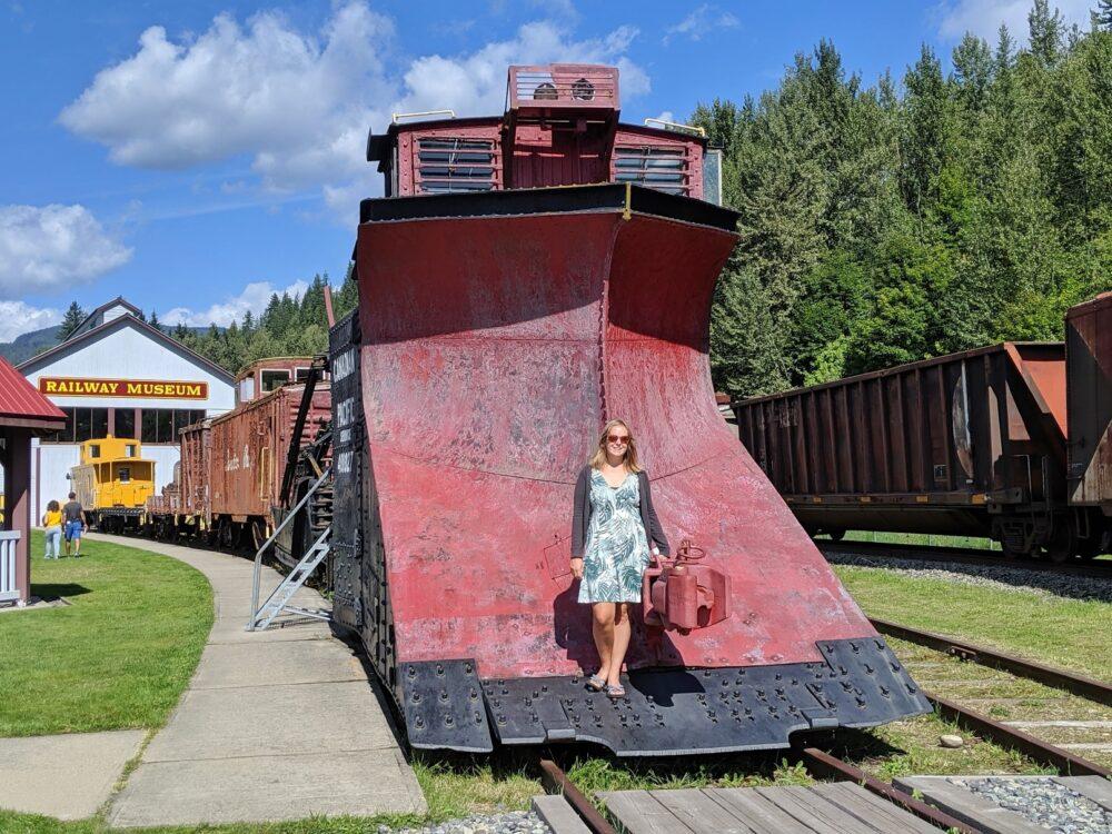 Gemma standing in front of huge snow plow from Revelstoke Railway Museum