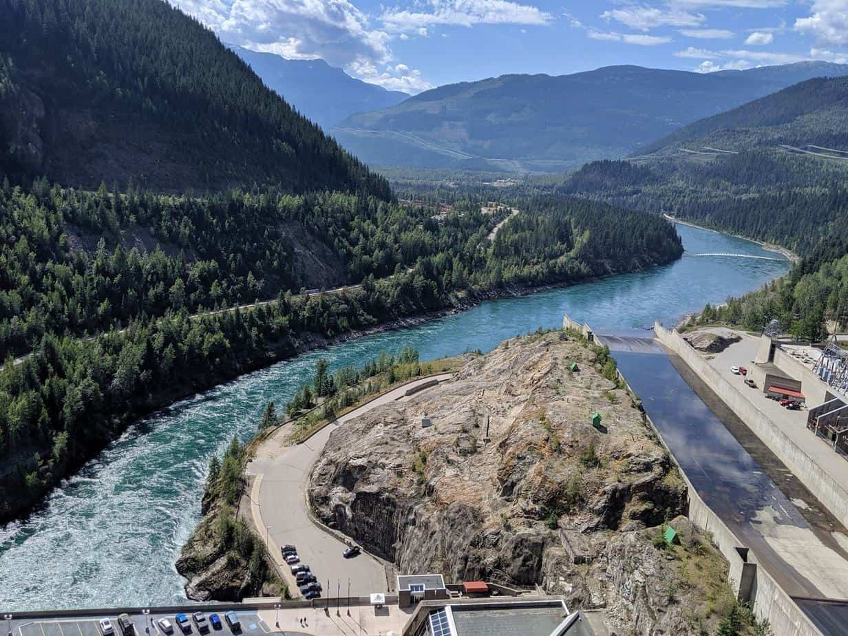 View from Revelstoke Dam lookout of Columbia River snaking into distance surrounded by mountains
