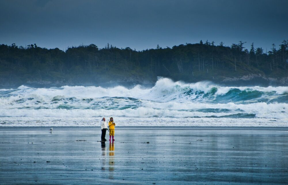 Two people stand on the beach and watch huge storm season waves
