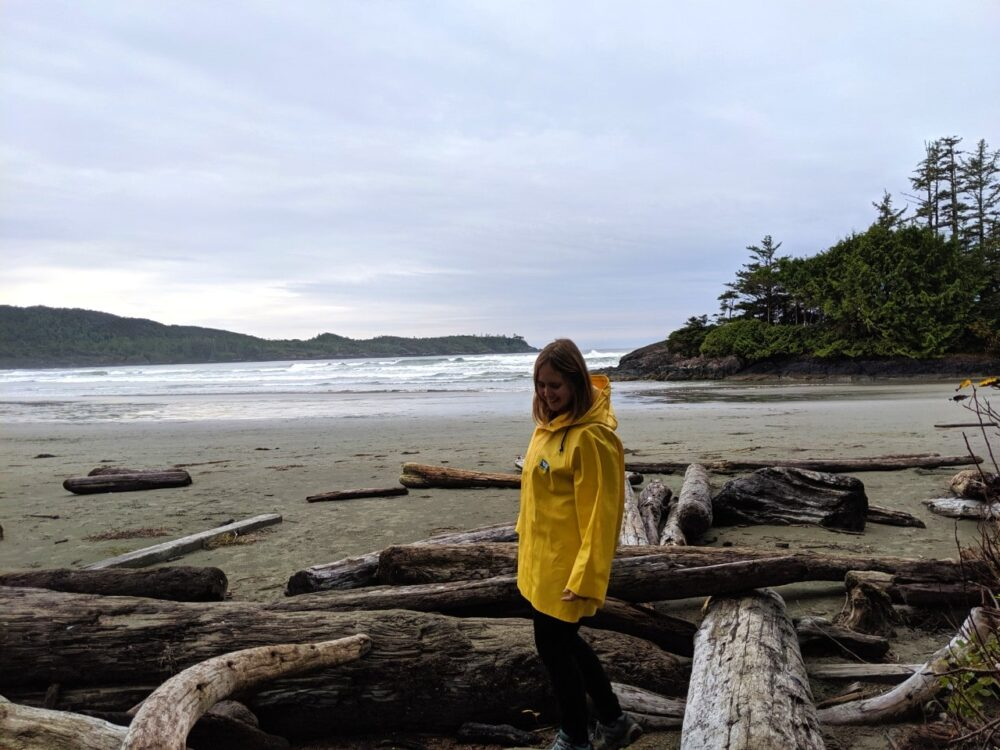 Gemma in a yellow rain jacket on Cox Bay beach