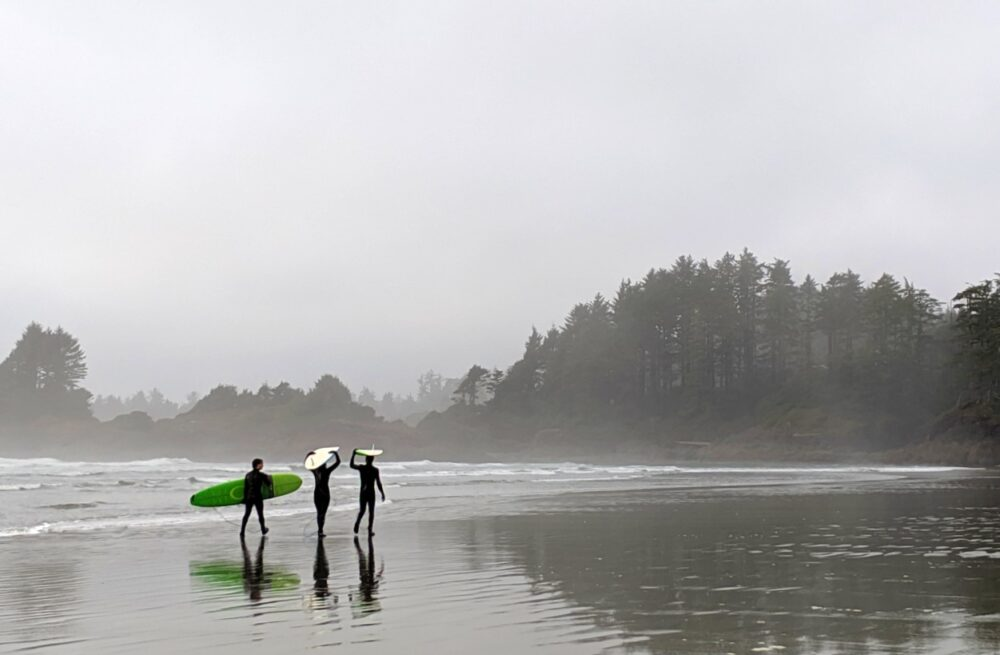 Three surfers walking along the beach in Tofino