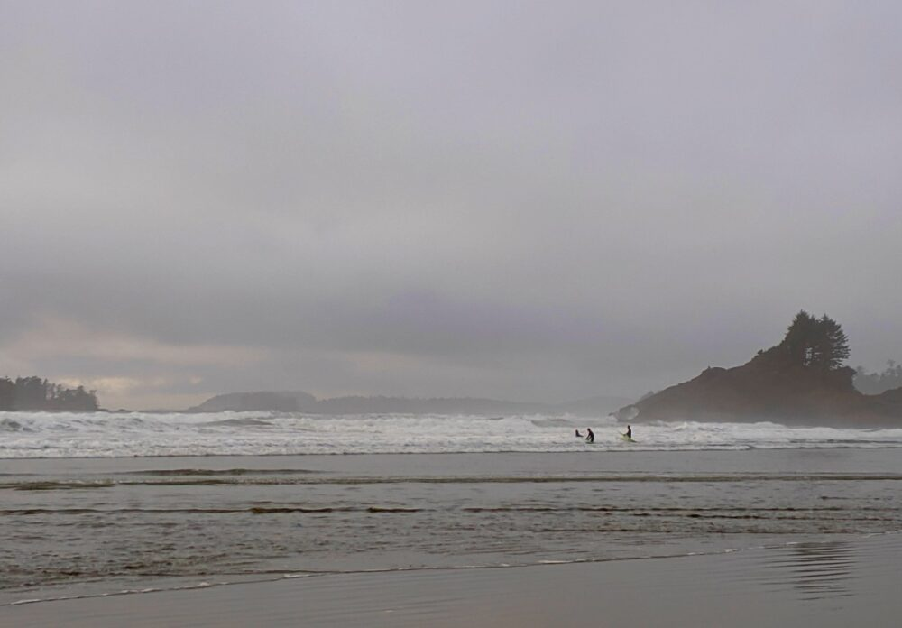 Three people surfing in big waves at Cox Bay, Tofino