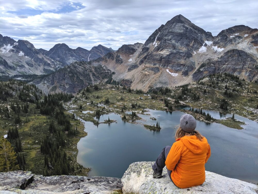 Gemma in orange jacket sitting on a rock, elevated over a beautiful lake bordered by mountains