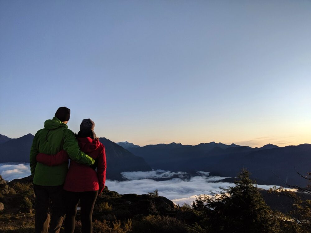 Gemma and JR standing with back to camera looking at sunrise from mountain summit