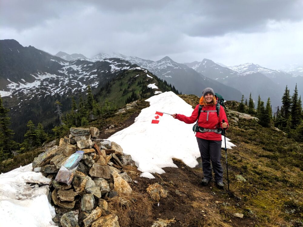 Gemma standing in red jacket next to cairn and snow pile on mountain ridge in Wells Gray Provincial Park