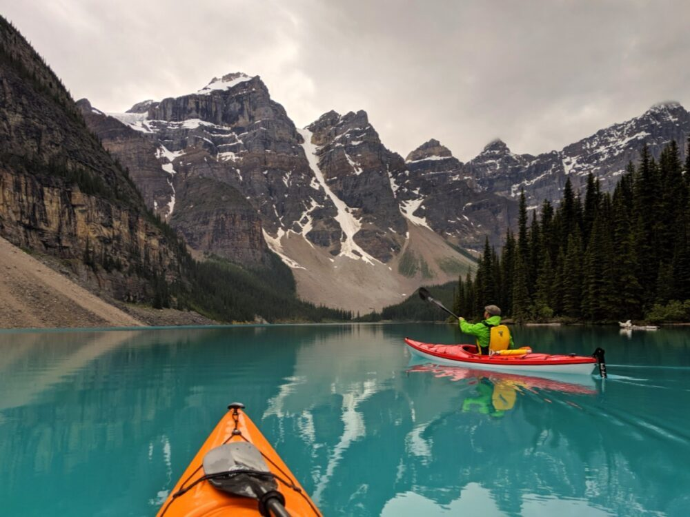 Kayak view of Moraine Lake with reflections of surrounding mountains, with JR in red kayak paddling away from camera