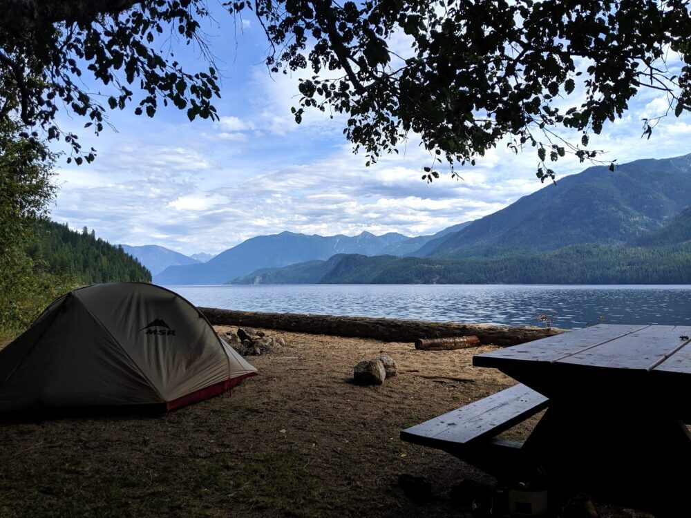 View of backcountry camping site with picnic table on right with set up tent on left, in front of calm lake with mountains bordering other side