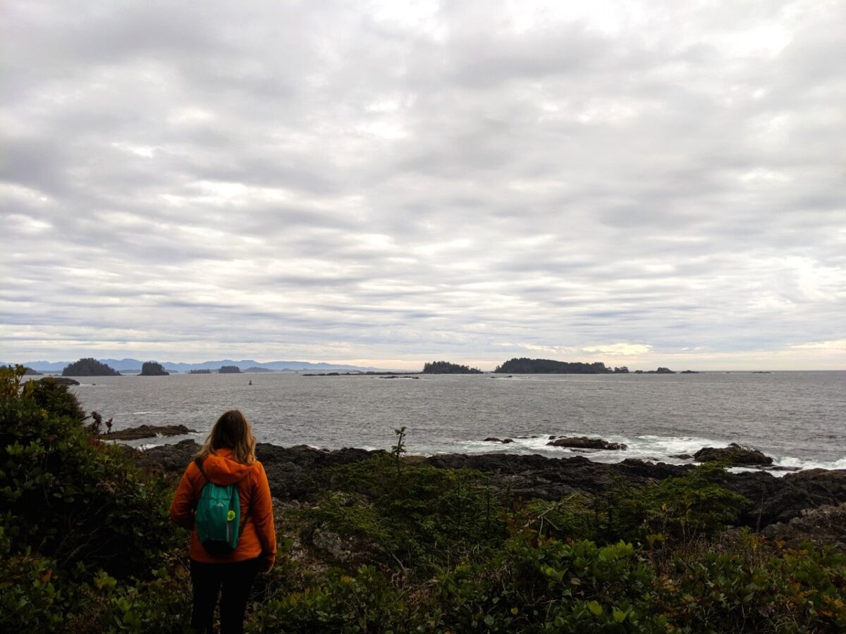Gemma stands with her back to camera, looking in the distance to islands in the pacific