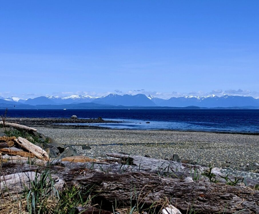 View looking out to a rocky beach with calm ocean and mountains beyond on Highway 19A near Campbell River