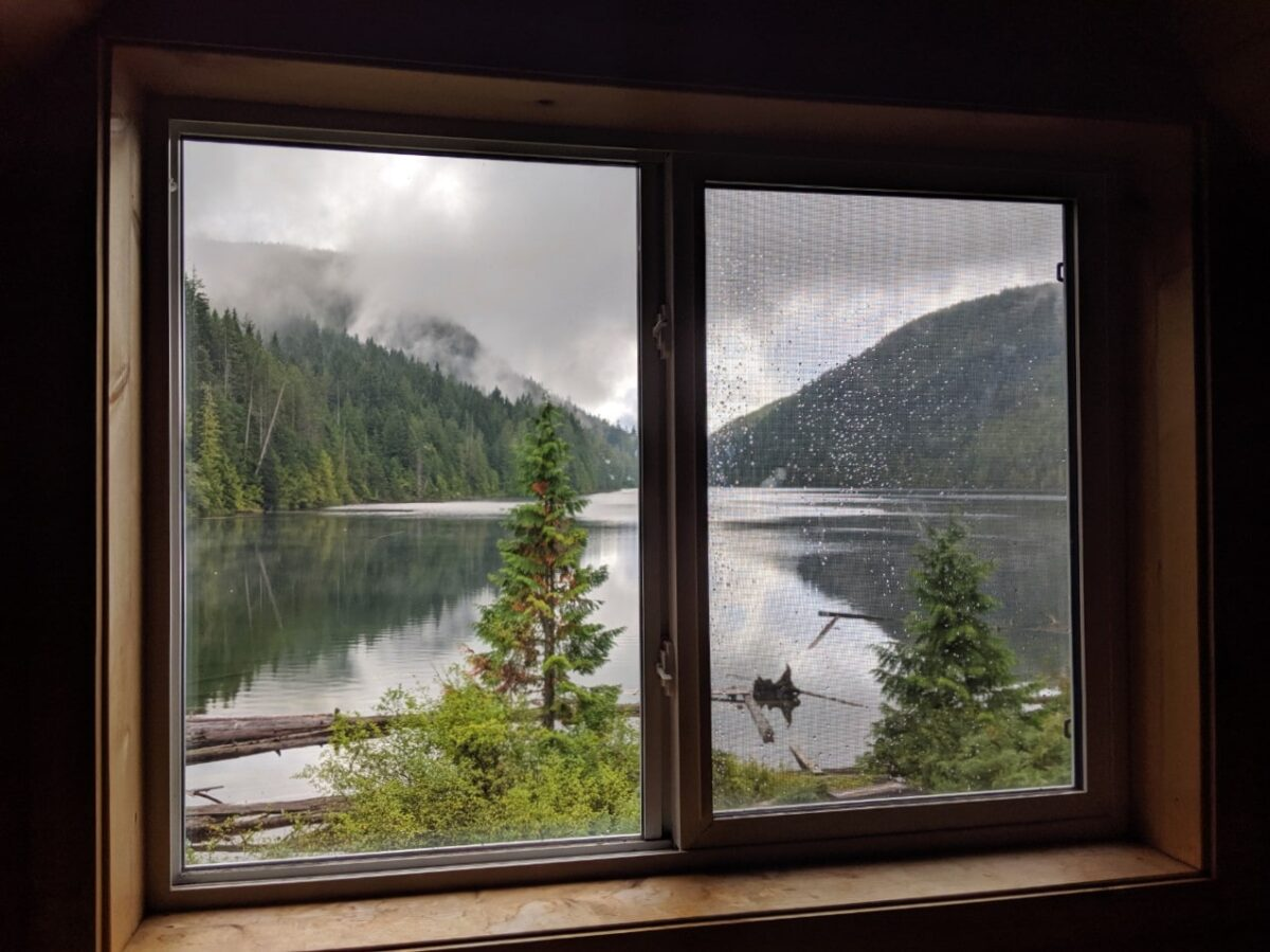 View looking through Confederation Lake hut upstairs window towards still lake and surrounding trees