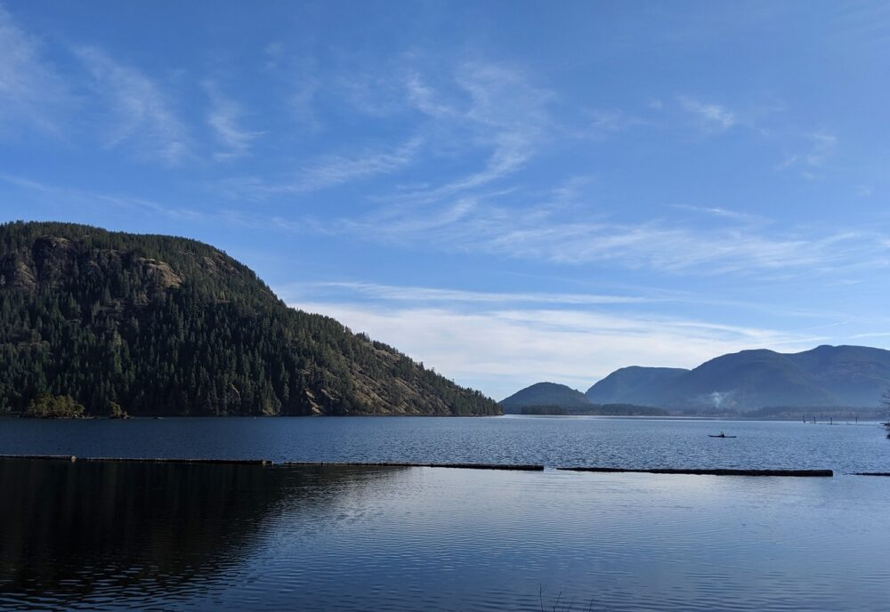 Calm Cowichan lake views with a kayaker paddling
