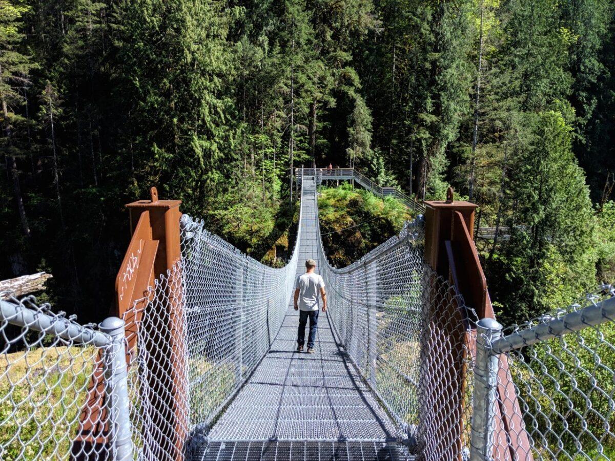 JR standing on suspension bridge above deep canyon