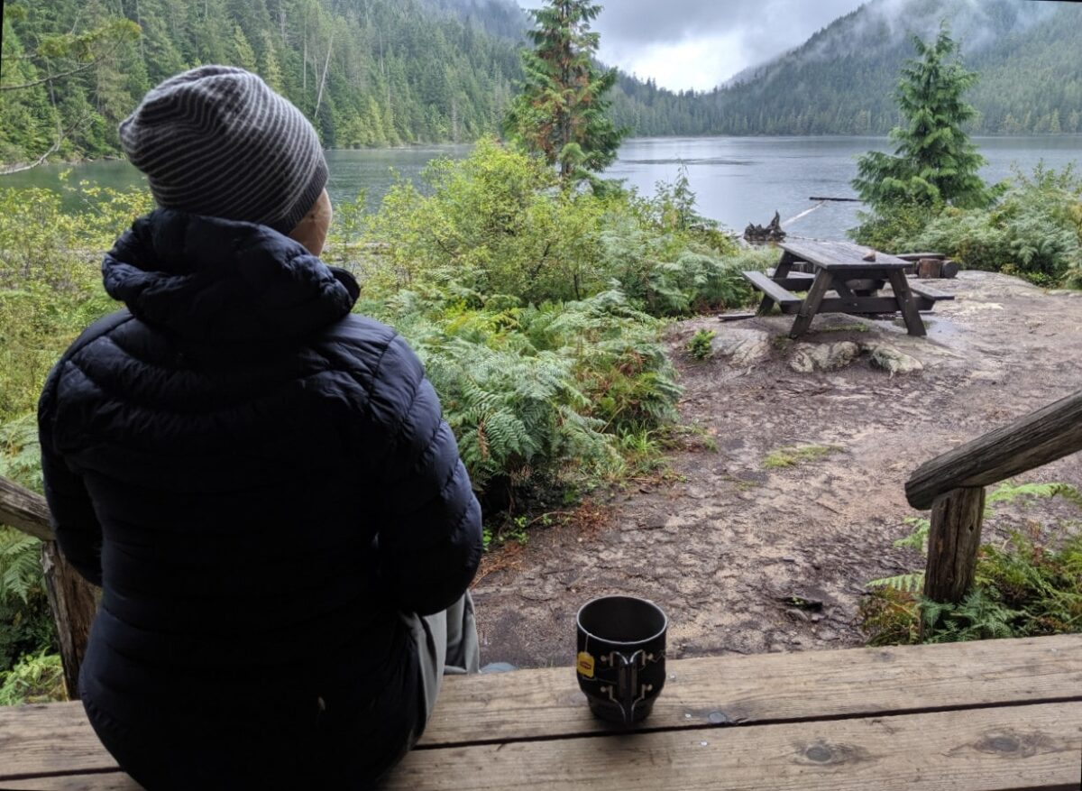 Gemma sat on the porch of the Confederation Lake Hut, looking out to the water