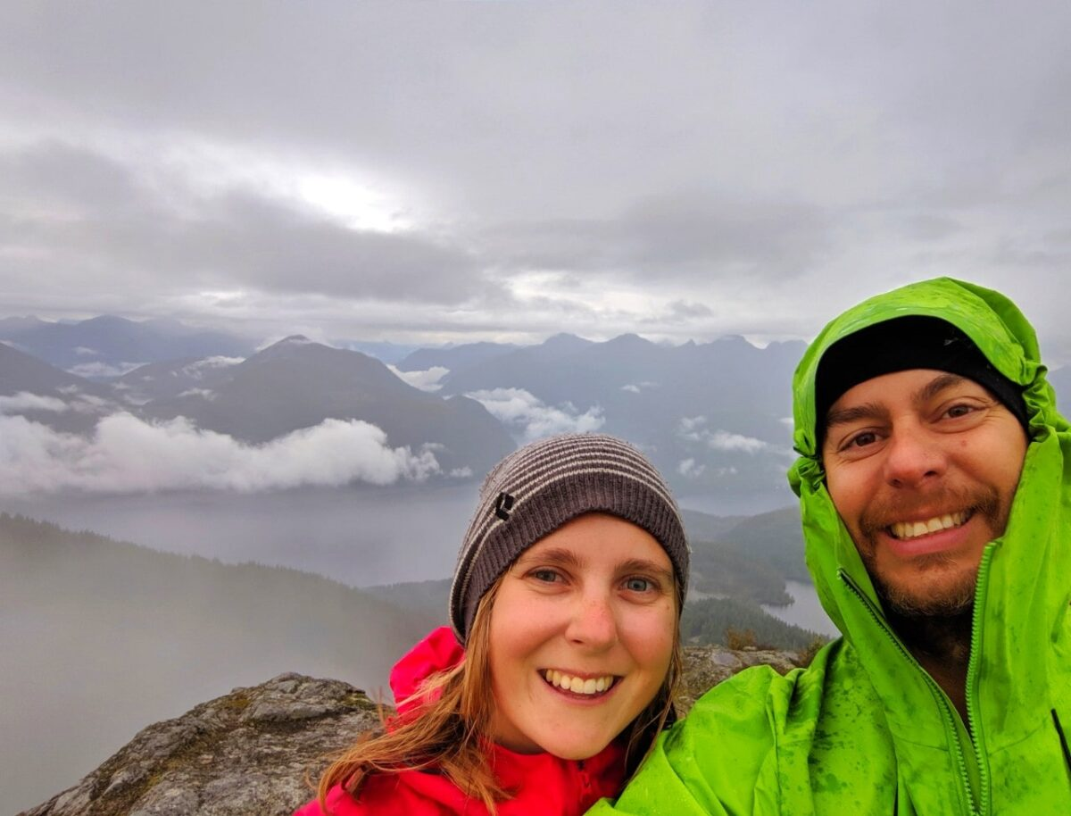 JR and Gemma selfie at the top of Tin Hat with cloudy and misty skies and glimpses of lakes below