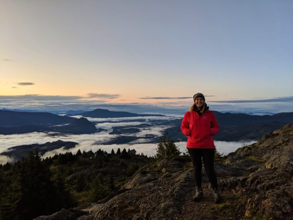 Gemma standing on mountain summit at sunrise with partial cloud over on mountains below