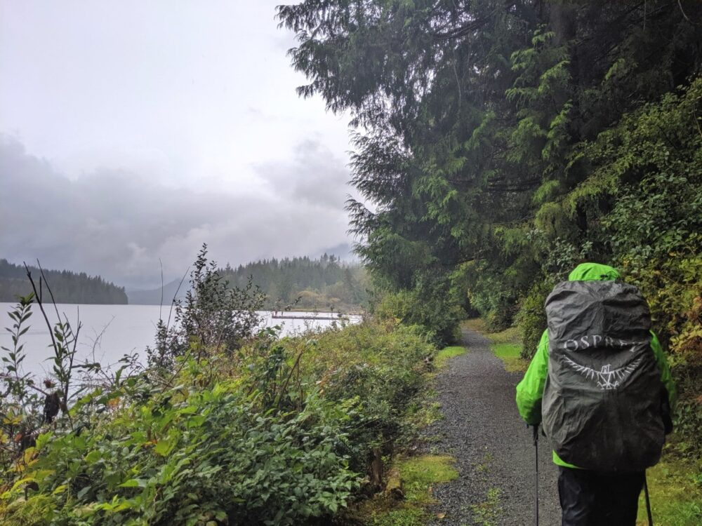 JR hiking next to lake on Sunshine Coast Trail with green rainjacket, hiking poles and an Osprey backpack raincover