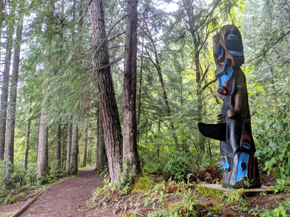 Colourful totem pole next to flat hiking path
