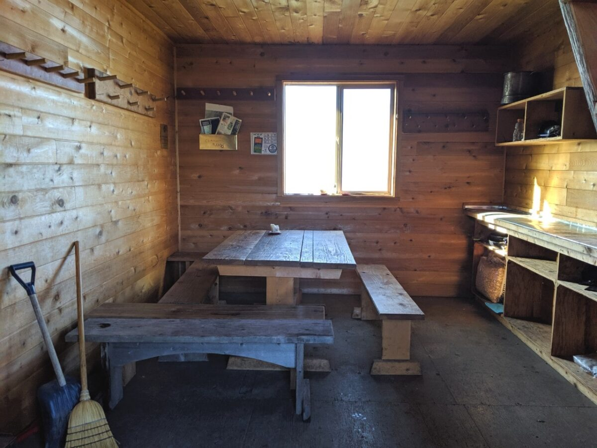 A view inside Tin Hat Mountain Hut with benches, kitchen counter, window and lots of wall hooks