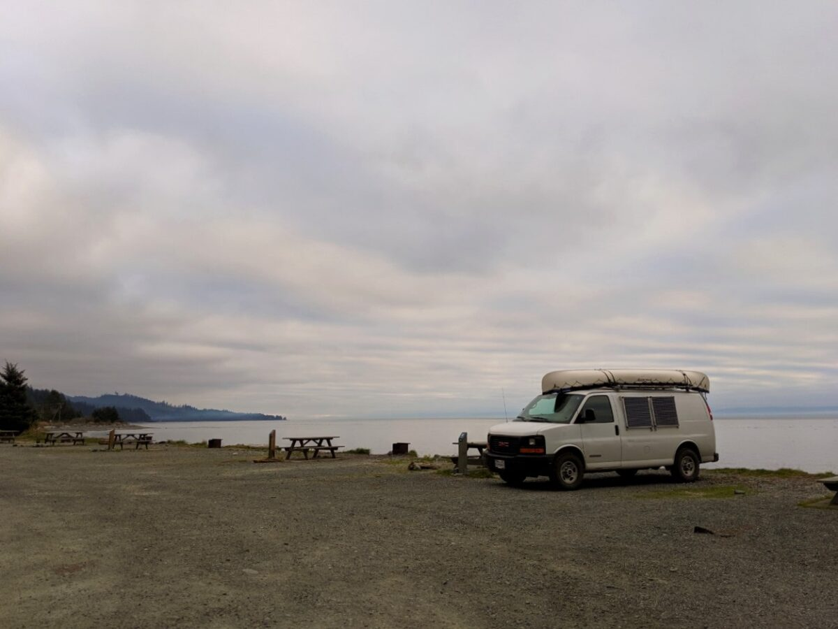Large gravel campground next to the ocean with picnic tables and fire pits. A white van is parked next to the one of the sites