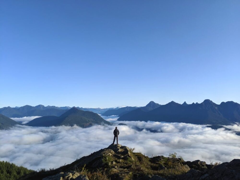 JR standing on a summit looking over mountain peaks and clouds