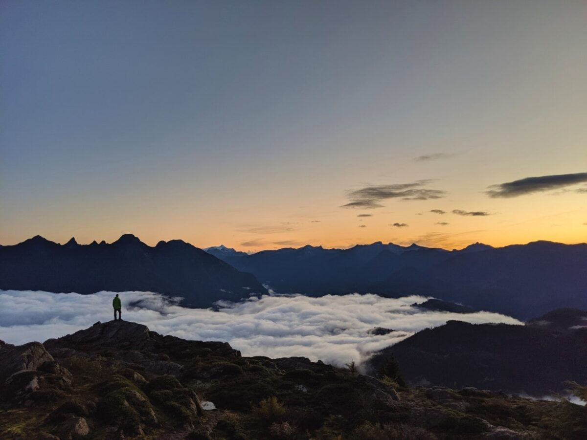 Lone figure on mountain ridge with clouds and mountains behind at sunrise