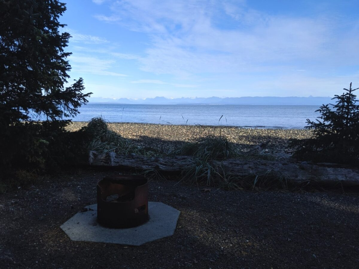 Campfire ring in front of a stony beach, calm ocean and mountains behind